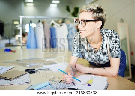 Happy self-employed designer of clothes drawing model of trendy dress for new author collection