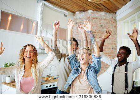 Ecstatic and laughing friends with raised hands dancing at party at home