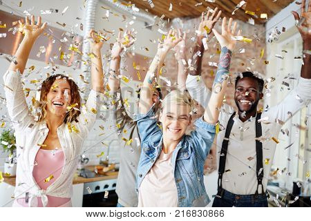 Young cheerful teenagers in casualwear dancing at xmas party under confetti rain
