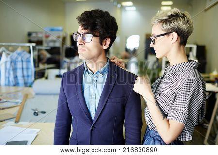 Young self-employed dressmaker taking measures of shoulder of client jacket