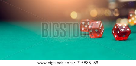 Red dices on green table, background with lights, blank background for text
