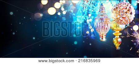Christmas and New Year Gold and Blue Decoration. Abstract Blurred Bokeh Holiday Background with beautiful baubles and Blinking Garland. Christmas Tree Lights Twinkling. Xmas backdrop art design. Wide