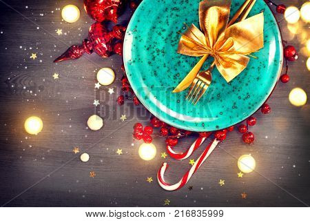 Christmas Holiday Dinner table setting. Tabletop, top view. Xmas table decoration with colorful decor and candles, Served with Gold cutlery on wooden table