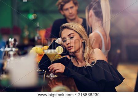 Picture showing young woman sitting alone in bar with a coctail