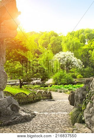 Walking gravel paths, decorative stones, lotus, bushes and trees in Humble Administrator's Garden, Suzhou, Jiangsu province, China. Summer day