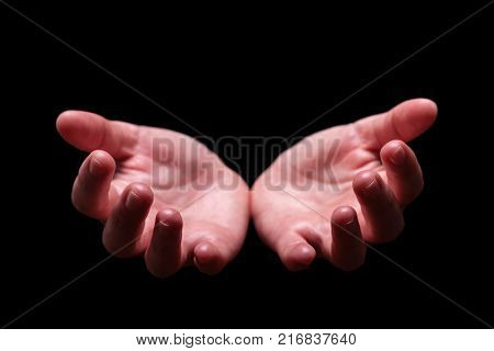 Woman hands cupped in a welcoming, accepting, offering, giving, begging, receiving gesture. Also for praying, prayer, welcome, accept, give, receive, protect, concept. Black background, front view