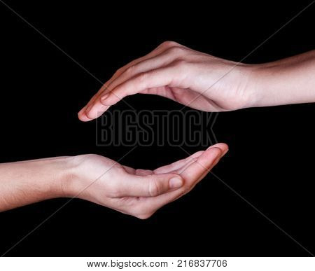 Woman or female hands cupped in a protection, protection, safety or safe concept symbol. Black background with copy space. Left and right hands