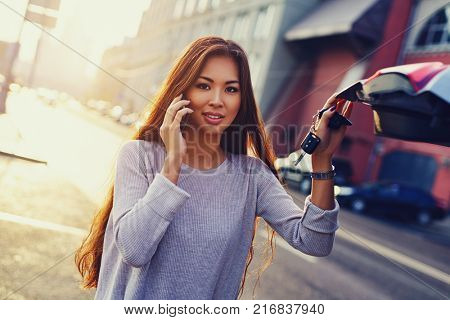 Young asian business woman with phone standing at the car with keys on morning city background