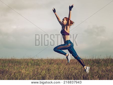 Young happy slim sports woman running and jumping on summer field