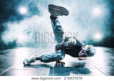 Young man break dancing in club with lights and smoke. Tattoo on body. Blue tint colors.