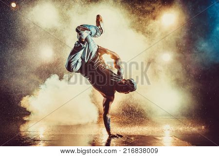 Young cool man break dancing in club with lights, smoke and water. Tattoo on body.