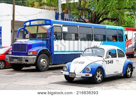Acapulco Mexico - May 30 2017: Taxi car Volkswagen Beetle and urban bus International 3800 in the city street.