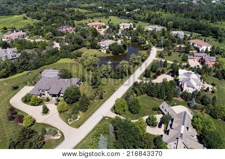 Aerial view of a luxury neighborhood with mature trees and a pond in a Chicago suburban neighborhood in summer. poster