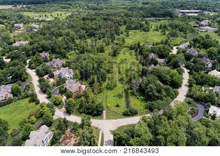 Aerial view of a luxury neighborhood with mature trees and a nature area in a Chicago suburban neighborhood in summer.