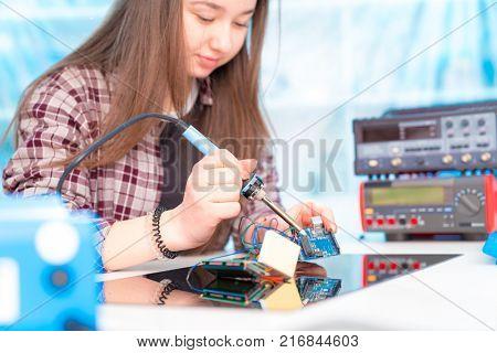 Schoolgirl in laboratory robots debug microcontroller