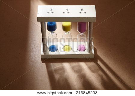 Sandglass, hourglass or egg timer on wooden floor with shadow showing the last second or last minute or time out