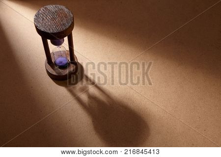 Sandglass, hourglass or egg timer on wooden floor with shadow showing the last second or last minute or time out. With copy space.