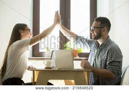 Teamwork concept: businessman and businesswoman giving high five and congratulating each other on success in teamwork. Millennial coworkers celebrating job victory