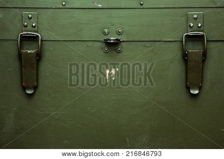 A green military storage box for ammunition. Green box from the war with scratches and locks in front.