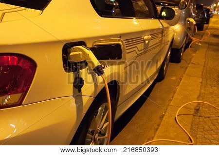 Electric cars charging at night in city street. Charging white electric car.