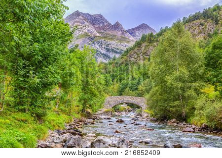 Image of a stone bridge over the River Gave de Gavarnie few kilometers downstream of the Cirque de Gavarnie in Pyrenees Mountains.
