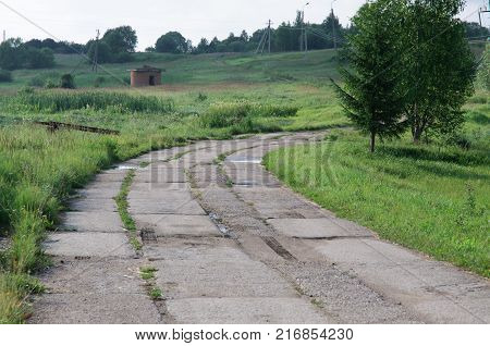 Old concrete road leaving far into the distance among meadows