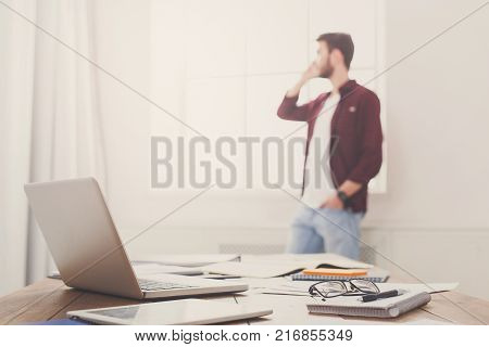 Business negotiations background. Businessman talking by mobile phone unfocused, selective focus on working table with laptop