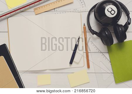 Education and work concept, top view shot of workplace. Stationery supplies blank notepad, pen, binder clips, ruler, paperclips and headphones on white wooden desktop