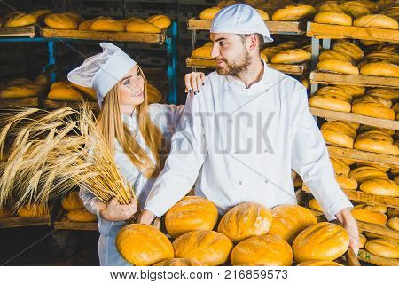 Bakery. Bread. Two bakers. Young beautiful workers of a bakery on a background of racks with bread. Industrial production of bakery products. Couple.