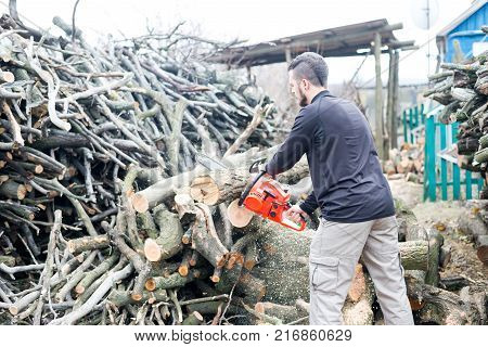 Young Man Is Sawing Logs Chainsaw Countryside.