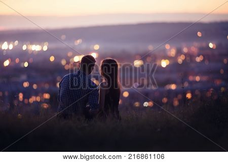 Lovers man and girl against background night city, night starry sky and horizon. Concept date Valentine's Day, first kiss love, forever together.