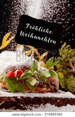 a black signboard with the text frohliche weihnachten, merry christmas in german, on a stollen cake sprinkled with icing sugar, placed on a wooden rustic table