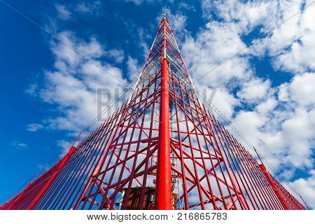 Telecommunication tower with panel antennas and radio antennas and satellite dishes for mobile communications (2G 3G 4G 5G) with red fence around tower against blue with clouds