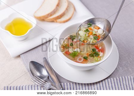 Fresh vegetable soup made of cabbage, carrot, potato, red bell pepper, in white bowl with cutlery