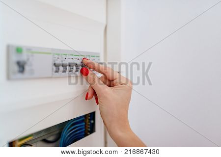 Woman Regulating Temperature On Home Heating Thermostat