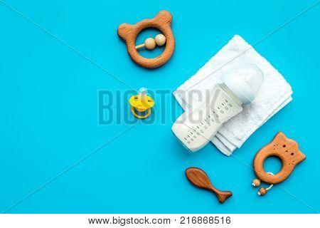Little baby background. Wooden toys, pacifier, bottle, towel on blue background top view.