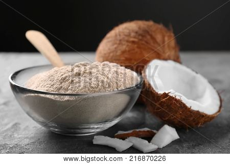 Glass bowl with coconut flour and fresh nuts on table