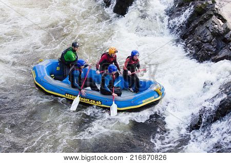 Llangollen Wales UK - January 28 2017: White water rafters on a team building exercise negotiating rapids on the River Dee in North Wales