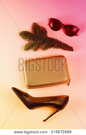 Hight heel shoes, bag and glasses with evergreen tree twig, dressing up for Christmas party, stylish flat lay scene, toned poster
