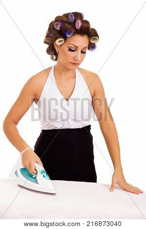 Cheerful housewife with an iron ironing clothes