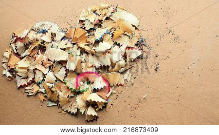 The volumetric shape of the heart, lined with pencil shavings. Multi colored pattern on a background of brown cardboard. The texture of pencil shavings of red, purple, green and blue colors