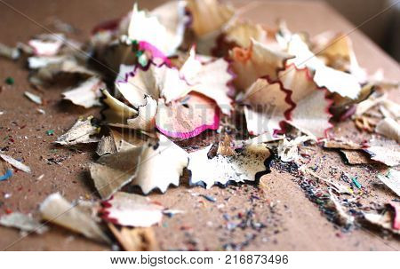 The texture of pencil shavings of red, purple, green and blue colors. Red and black shavings, lit by bright sun, in the center of the frame.