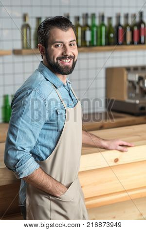 Good mood. Cheerful responsible young waiter feeling happy to be at work while standing and smiling friendly
