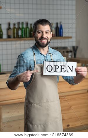 Open. Clever enthusiastic young owner of a cafe feeling excited after opening an amazing comfortable cafe while standing with the sign and smiling