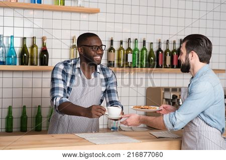 Teamwork. Handsome friendly helpful waiter standing at the bar counter while giving a cup of coffee to his cheerful responsible colleague