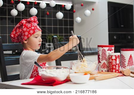 The Boy In The Christmas Cap Of The Cook And Apron Helps Her Mother Cook Cookies With Ginger In A Li