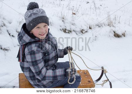 Little boy enjoying a sleigh ride. Child sledding. Toddler kid riding a sledge. Children play outdoors in snow. Kids sled in mountains in winter. Outdoor fun for family Christmas vacation.