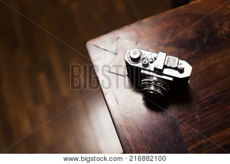 Old range finder camera on a wooden table, in a dark room. Extremely shallow depth of field.