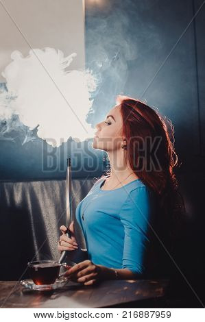 Red-haired Sexy Girl In A Cafe Smoking A Hookah Dressed In A Blue Blouse