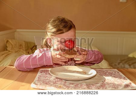 Kid girl playlful eats chocolate cream spread on bread. Chocolate sweet food snack. Happy girl has a snack in the kitchen. A cute small girl smiles. A small girl with chocolate cream stains on face. Little girl wears clown nose. Childhood and fun concept